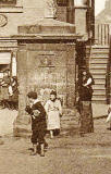 Zoom-in to the old well in front of John Knox House in the Royla Mile, Edinburgh  - Detail from a Postcard by W J Hay in the 'Knox Series'