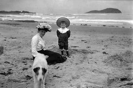 Nurse Annie and Tommy with dog, and Craigleith Island in the background  -  Around 1905