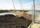 Reclaiming the land in Granton Western Harbour  -  looking to the north-west from Middle Pier towards pile driving in the harbour  -  July 2004