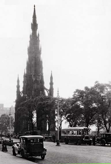 The Scott Monument in Princes Street with two old cars and a single deck Edinburgh Corporation bus