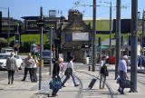 Edinburgh Tram Service  -Travellers at Haymarket, heading forHaymarket Station cross the tram lines in front of the tram  -  June 2014