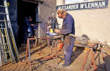 Alexander McLennan working in the yard outside his blacksmiths workshop at Dunedin Street, Powderhall