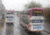 Photo taken in the rain from the front seat on the upper deck of a Lothian Bus  -  Two Buses on Route 22 in Princes Street