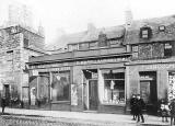 Where and when was this photograph of a row of shops, including E Kane, Hairdresser, taken?